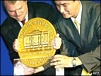 Two men try to move what Austria says is the world's biggest world coin