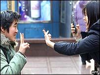 Un par de japoneses se sacan fotos con un celular