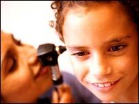 Doctor checking girl's ear