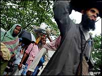 Bangladeshi men carry their belongings on their heads after their homes were destroyed by a tornado in the village of Kamarpara, north of Dhaka, 7 October 2004