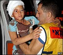 An injured Israeli child is carried by a rescuer after the Taba blast