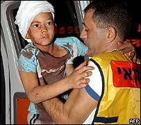 رجل اسعاف اسرائيلي يحمل طفلا مصابا