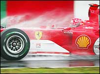 Michael Schumacher's car has plumes of spray coming off it in Japan
