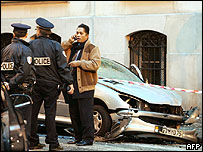 French policemen stand by car destroyed in embassy blast