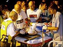 Ambulance staff treat a blast victim near the Taba Hilton