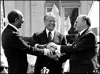 Egypt's Anwar Sadat and Israel's Menachem Begin shake hands with US President Jimmy Carter