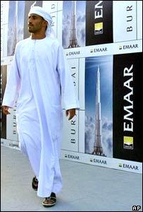 A man walks past billboard images of tower development Burj Dubai