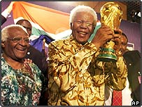 Former South African President Nelson Mandela holding the World Cup trophy watched by  Archbishop Desmond Tutu, left
