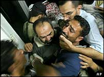 Relatives of policeman Emad Bader react after seeing his body in the morgue at Nasser Hospital in Khan Younis