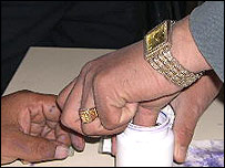 An Afghan voter is marked with ink
