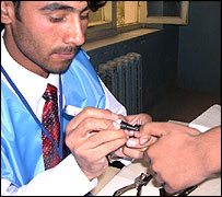 Applying indelible ink to a voter's fingernail