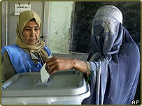 An Afghan veiled woman casts her vote for election at a polling station in Herat, Afghanistan