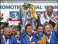 Shrewsbury captain Darren Tinson holds the trophy aloft after his side's play-off final win over Aldershot