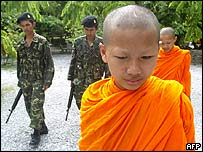 Thai soldiers provide security to monks while patrolling a Buddhist temple in the south