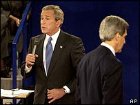 George W Bush answers a question as John Kerry returns to his stool