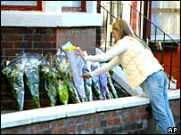 A mourner leaves flowers outside Mr Bigley's Liverpool home