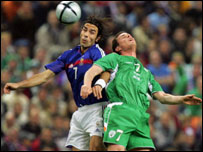 Robert Pires and Steve Finnan have an aerial duel