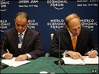 Israel's deputy prime minister and minister for trade and industry, Ehud Olmert (right), signs the deal with Mohammad Halaiqah, his Jordanian counterpart