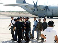 Illegal immigrants are escorted onto a plane by Italian police