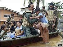 An Indian soldier lifts a boy onto a rescue boat in Assam