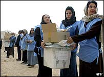 Afghan election workers pass ballot boxes along a line to be carried for vote counting in Kabul