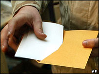 Absentee voter places vote in an envelope