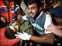 A Palestinian man weeps as he arrives at hospital with a man killed in an Israeli missile strike