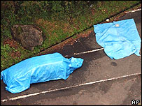 A blue sheet is covered on a car, left, where seven young men and women were found dead in a mountainside lot at Minano, near Tokyo, on Tuesday October 12, 2004