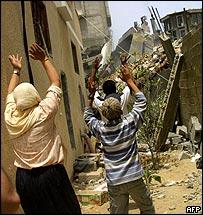 An Israeli army bulldozer demolishes a building in Rafah in the Gaza Strip