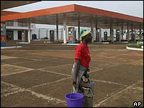 Woman walks past deserted petrol station