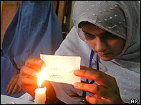 A polling agent checks the registration card of Afghan refugee in Peshawar, Pakistan