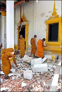 Thai Buddhist monks inspect the scene at one of the Buddhist temples damaged by bombs in Narathiwat province, southern Thailand, 17 May 2004