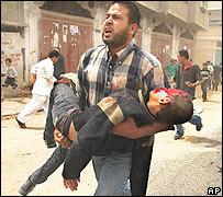 Un padre carga a su hijo herido en el ataque.