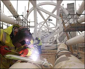 A workman welds a section of arch