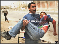 A Palestinian man carries a badly wounded child following a Israeli missile strike on a demonstration in the Rafah refugee camp