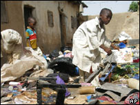 Muslim children scavenge the charred remains of property belonging to Christian settlers in Kano