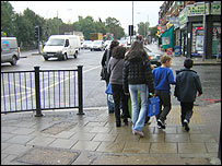 Mothers and children crossing the road