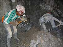 Miners shovel the rock