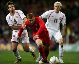 James Collins of Wales battles for the ball with Poland's Maciej Zurawski  and Piotr Wlodarczyk