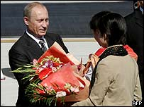 Russian President Vladimir Putin receives flowers upon arriving in Beijing airport, 14 October 2004
