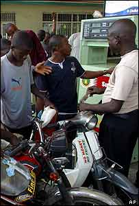 Nigerian two-wheel taxi drivers at fuel pump