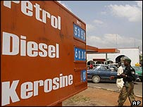 Nigerian policeman walks past a petrol station on 12 October as cars queue to get fuel