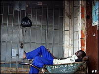 A worker sleeps in front of a closed shop in Abuja on 12 October