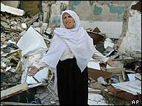 A Rafah woman stand in front of her destroyed home