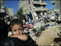 A Palestinian boy and his mother sit in the rubble of their house in the Brazil section of the Rafah refugee camp