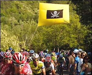 The peloton passes a pirate flag hung across the road to honour the late Italian rider Marco Pantani,