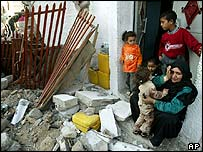 Palestinian family in front of destroyed house
