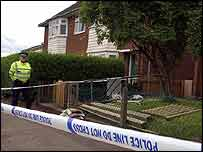 An officer by a cordoned off house near the scene of the fatal stabbing