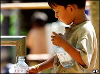 Cambodian boy filling bottle
