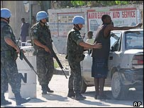 Brazilian UN peacekeepers search a man at a checkpoint in Port-au-Prince